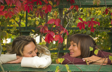 Two girls having a rest in autumn park