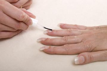 Applying clear nail varnish to acrylic finger nails