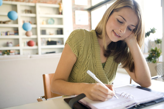 A young woman writing in her agenda