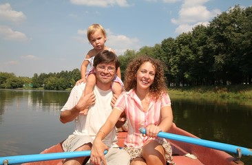 The family  on a boat on the river