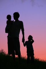 father with two children against sunset