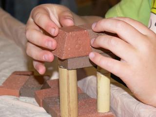 Kinderhände beim Bauen mit Holz und Tonsteinen