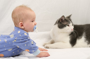 Baby and cat on white muslin