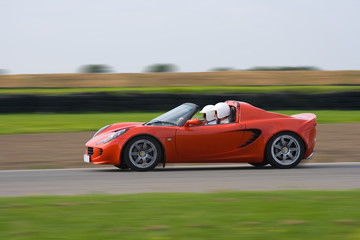 Printed roller blinds Fast cars Bright red sports car at speed on a race circuit