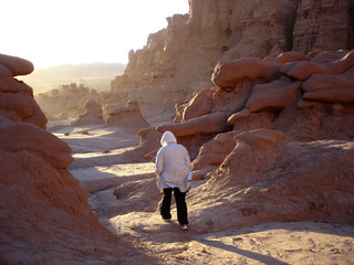 tourist walking through goblin formations on windy afternoon
