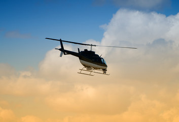 Rear view of helicopter in flight at sunrise