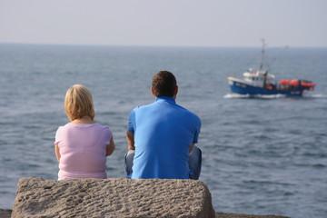 Couple watching fishing boat