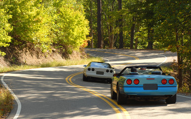 Two sports cars driving on a winding road Wall mural