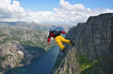 base-jumper falling from cliff down to the fjord