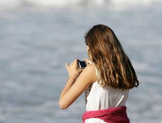 jeune fille entrain de photographier avec un compact numérique