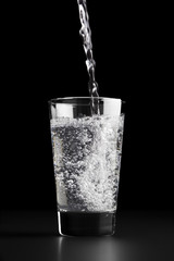 Pouring a glass of water against a black background