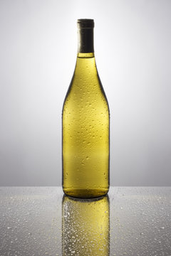 Bottle of white wine on a reflective tabletop.
