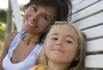 Portrait of mother and daughter sitting on the bench