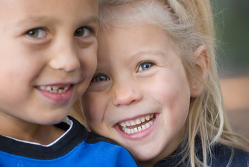 Cute blonde girl smiling with her big brother slightly blurred