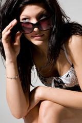 Sitzendes Mädchen mit  Sonnenbrille in der Hand