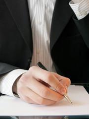 homme d'affaire écrivant avec un stylo