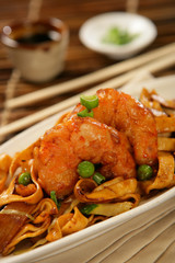 Deep fried scampi with Asian noodles and green peas