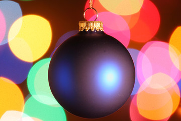 Blue Christmas ornament with colorful lights in background.