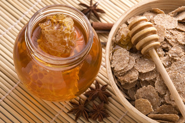Foto auf Leinwand Bienen fresh honey with honeycomb, spices and breakfast flakes