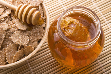 Foto auf Leinwand Bienen fresh honey with honeycomb and breakfast flakes