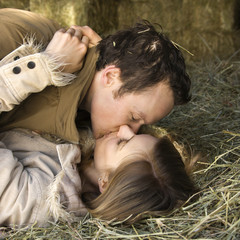 Kissing couple in hay.