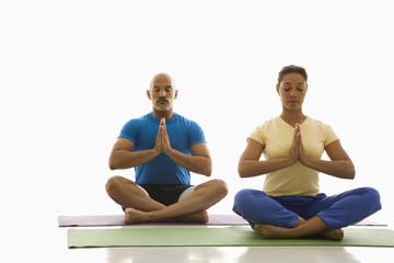Two people practicing yoga.
