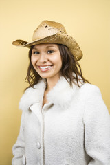 Woman wearing cowboy hat smiling at viewer.