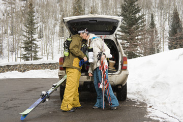 Young couple standing by vehicle with ski equipment kissing.
