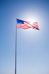American flag blowing in clear blue sky.
