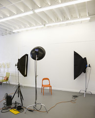 Studio shot of photographic lights aimed at red plastic chair.
