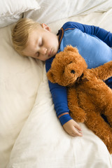 Child sleeping with teddy.