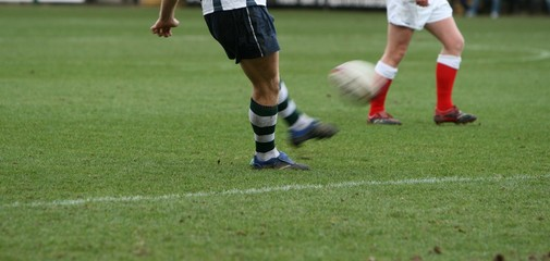 kicking rugby ball with motion blur