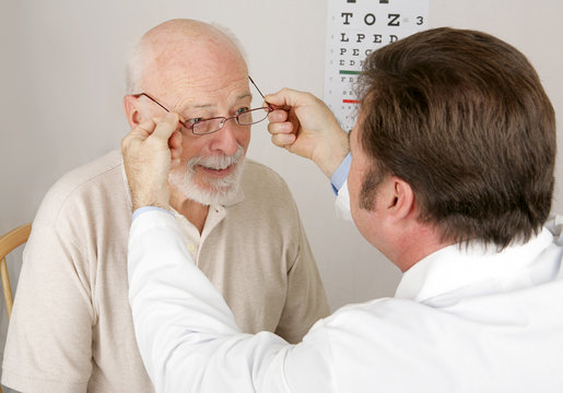 Optician putting a new pair of reading glasses on a patient.