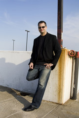 Casual Male Leaning Against Wall With Sunglasses