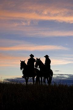 Cowboys silhouettes against a dawn sky. Horse ranch in Montana