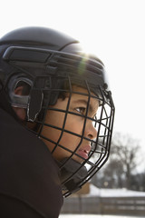 Close up of ice hockey player boy in cage helmet.