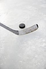 Close up of ice hockey stick on ice rink.