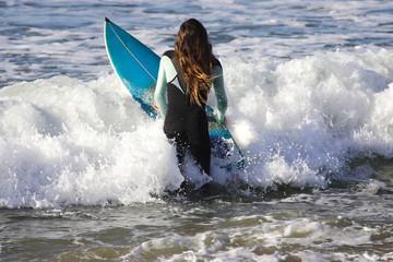fille aux cheveux longs qui rentre à l'eau avec sa planche