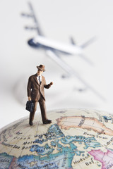 Business figurine, earth globe, toy airplane in background