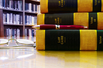 Law books stacked in a library, with pen and glasses