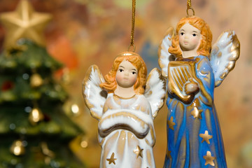 Ceramic angel toys hanging against colorful background.