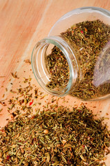Jar of mixed herbs on a table..