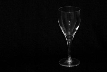 single wine glass shot against a black background