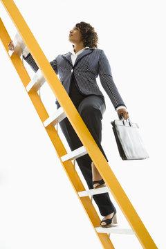 Businesswoman holding briefcase climbing ladder.
