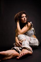 Sitzendes Mädchen mit Hose aus Zeitungen