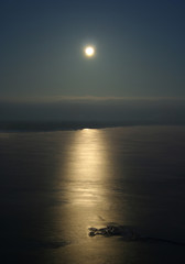 Full moon over the ocean with moon path