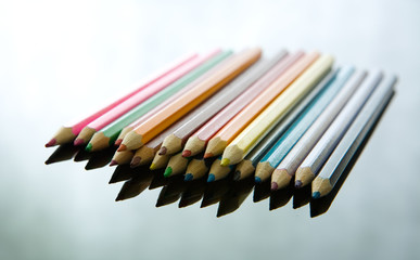 Multicolored pens on reflective background