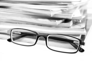 stack of magazines and eyeglasses isolated on white
