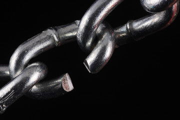 Chain with a cut link on a black background