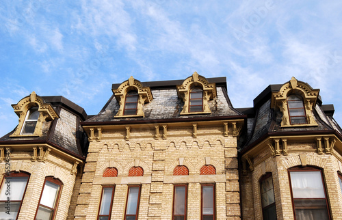 Yellow Brick Victorian House With Mansard Roof And Dormers